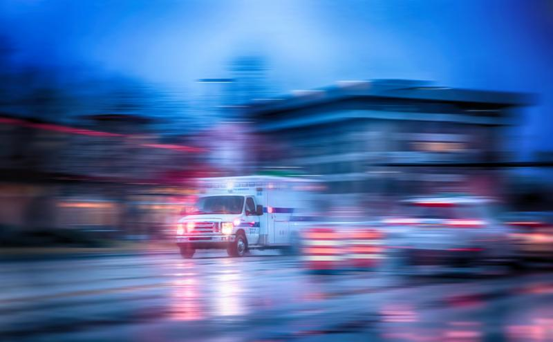 an ambulance racing through the rain on a stormy night with motion blur  NO SHARP FOCUS DUE TO RAIN and slow shutter speed  with reflections in the road