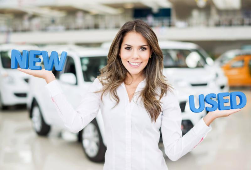 woman in car dealership with the word new in right hand and the word used in left hand