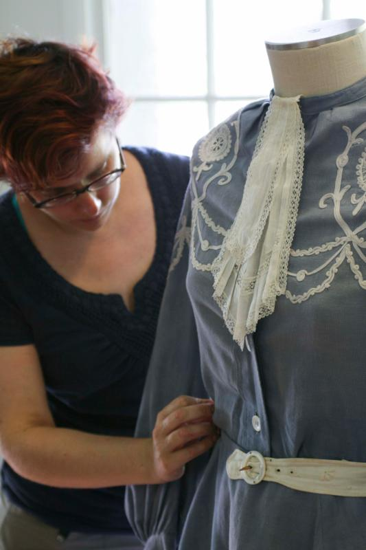 Texas profess of costume design examines a piece from our historic costume collection