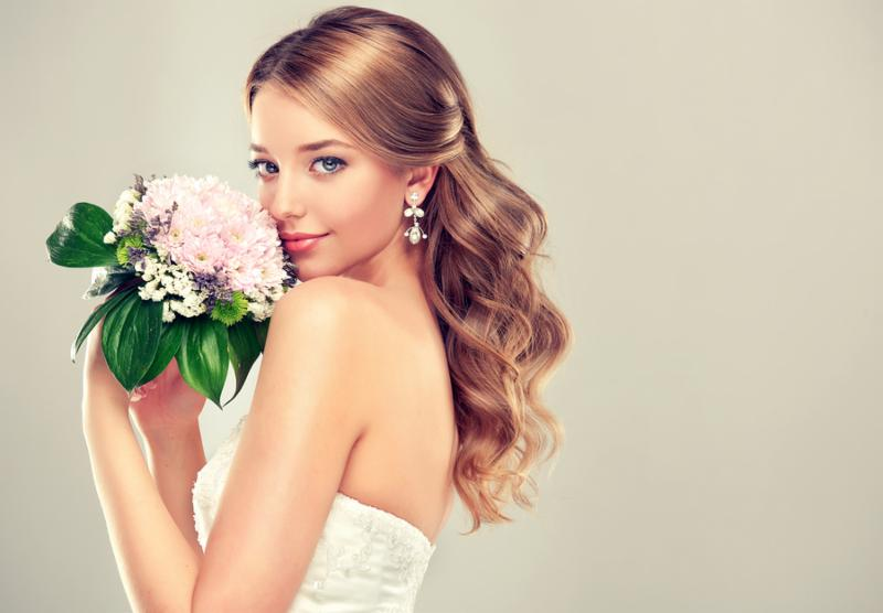 Girl bride  in wedding   white dress with elegant hairstyle and with a wedding bouquet