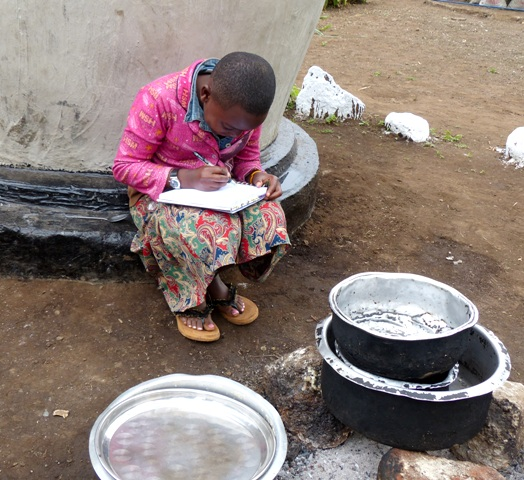 hands-on science for child observing three-stone fire vs. stove from ICSEE