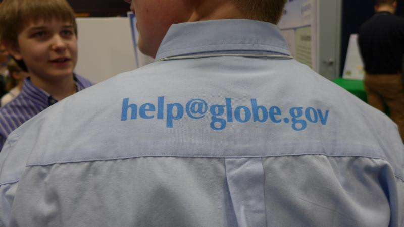 A man wearing a collar shirt with help@globe.gov on it.
