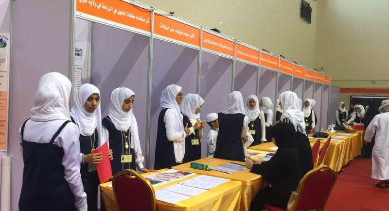 Students standing around the table at the Oman Science Fair.