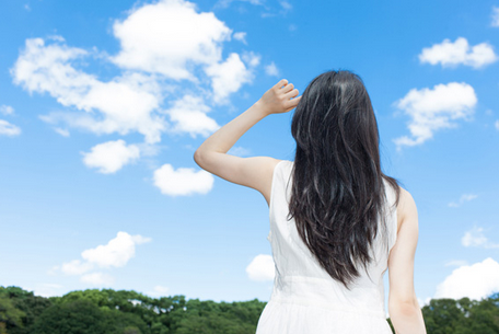 A woman looks at clouds in a bright blue sky.