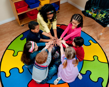 young children and teacher in a circle touching hands
