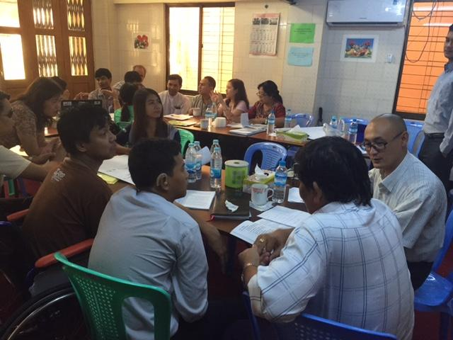 A group of more than 15 people are seated around conference tables engaged in a workshop