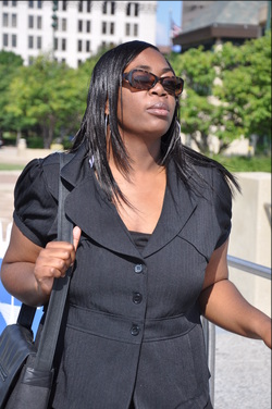 Woman with shoulder length hair, a black suit jacket, and sun glasses poses outside near a patch of greenery in an otherwise urban environment.