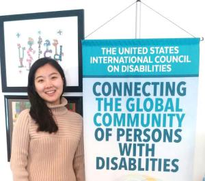 Semin Seo stands next to USICD Banner which says The United States International Council on Disabilities  Connecting the Global Community of Persons with Disabilities