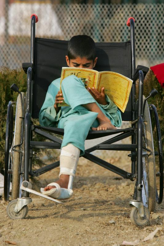 A young boy sits, cross legged, in a wheelchair too large for him, while intently reading a book.