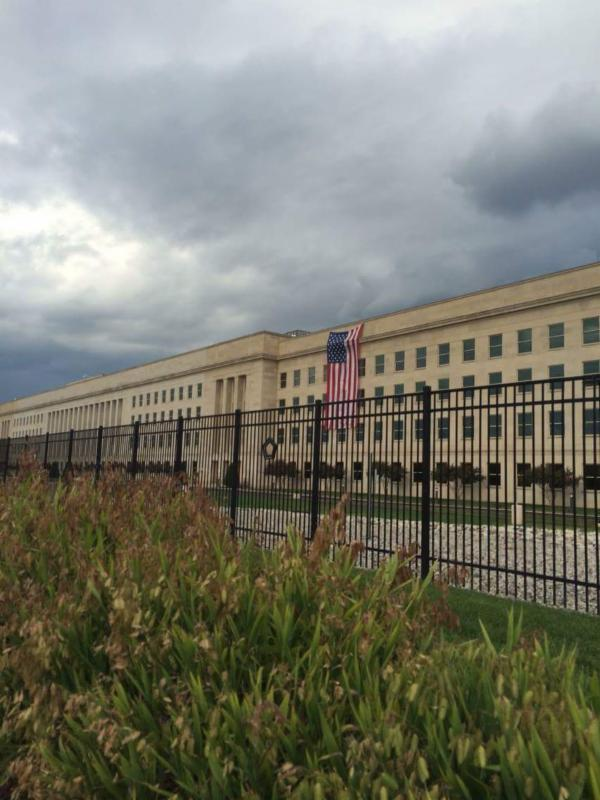 Picture of an overcast sky over the Pentagon, which has a large US flag draped on it covering some of its upper floor windws