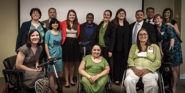 Fourteen people pose, standing and sitting in two rows, smiling for the camera. Most are in suits or dresses.