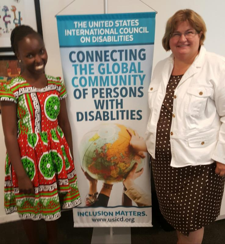 Beth Wanjiku Mdirangu and Isabel Hodge stand with USICD banner with a picture of hands holding a globe with the slogan Connecting the Global Community of Persons with Disabilities