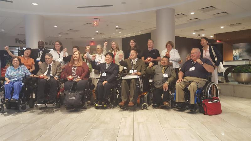 Two rows of people smiling at camera some standing some seated in wheelchairs