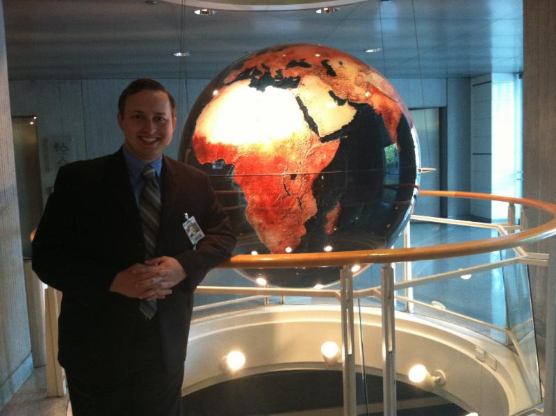 Young man stands in front of a large globe