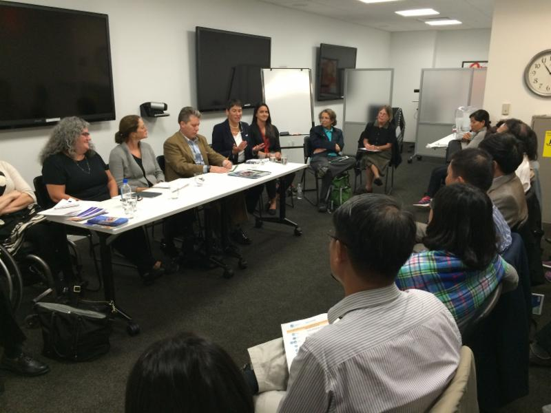 Panel speakers are seated at a table in front of an audience of visitors from Vietnam