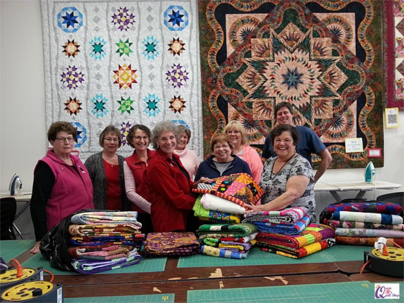 Group photo of Queen B's Quilt Shop Donation Workshop members and supporters presenting quilts to Elderly Make a Wish Foundation. December 2016