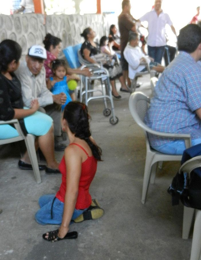 Woman on her knees using sandals to protect her hands while crawling. She faces a line of seated people waiting for wheelchairs.