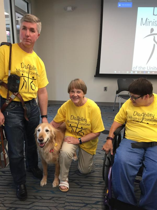 Eric stands with his guide dog_ Susan knees next to him_ and Lisa looks on from where she is seated in her wheelchair