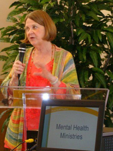 Susan in colorful top and sweater speaks into a microphone and stands behind a lecturn with Mental Health Ministries sign