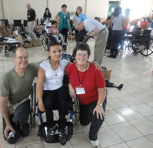 A man and a woman kneel next to a young woman in her new wheelchair with other wheelchair team members working in the background