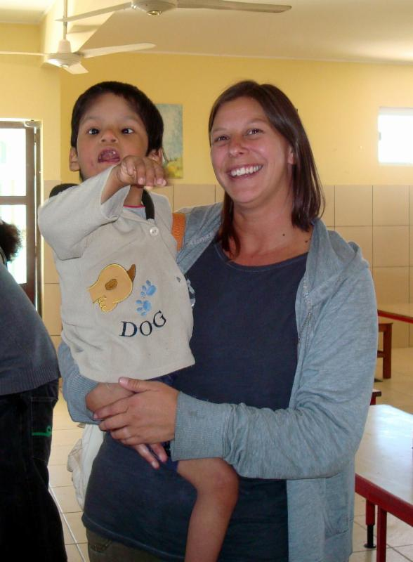 Smiling woman  standing_ holding a young boy who has a developmental disability_ with a crib style bed in the background