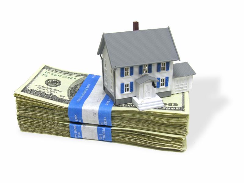 model of house sitting on stack of dollar bills