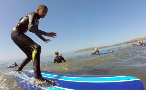 Boy surfing at Doran Beach Surf Camp