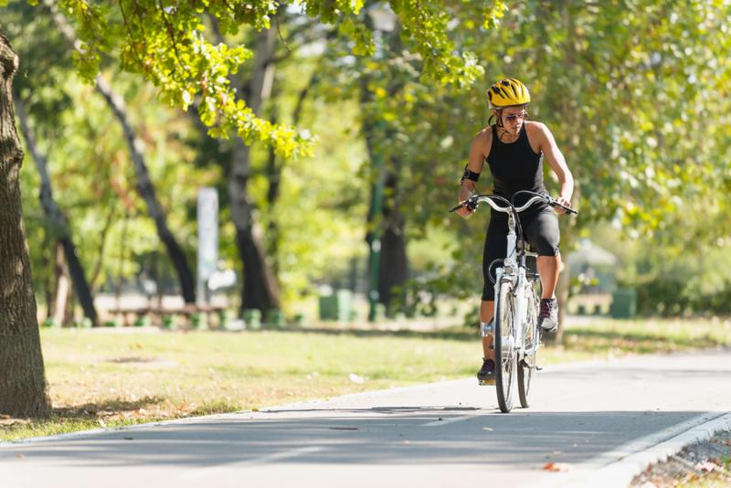 Young woman riding electric bicycle or e-bike in park