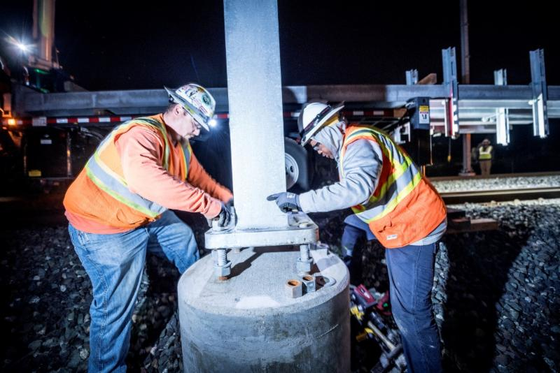 Crew installing a pole for Caltrain Electrification