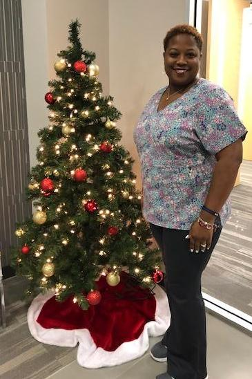 caregiver standing next to Christmas tree