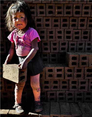 Small child labors to move bricks