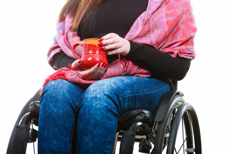 Disability drink relax leisure concept. Crippled lady on wheelchair. Disabled girl holding red cup drinking beverage.