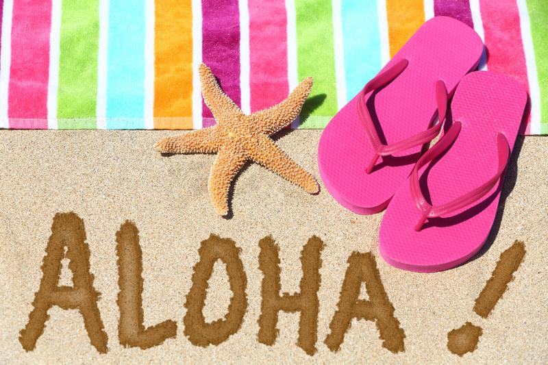 Hawaii beach travel concept. ALOHA text written in sand with water next to beach towel and summer sandals and starfish. Hawaiian vacation holidays background.