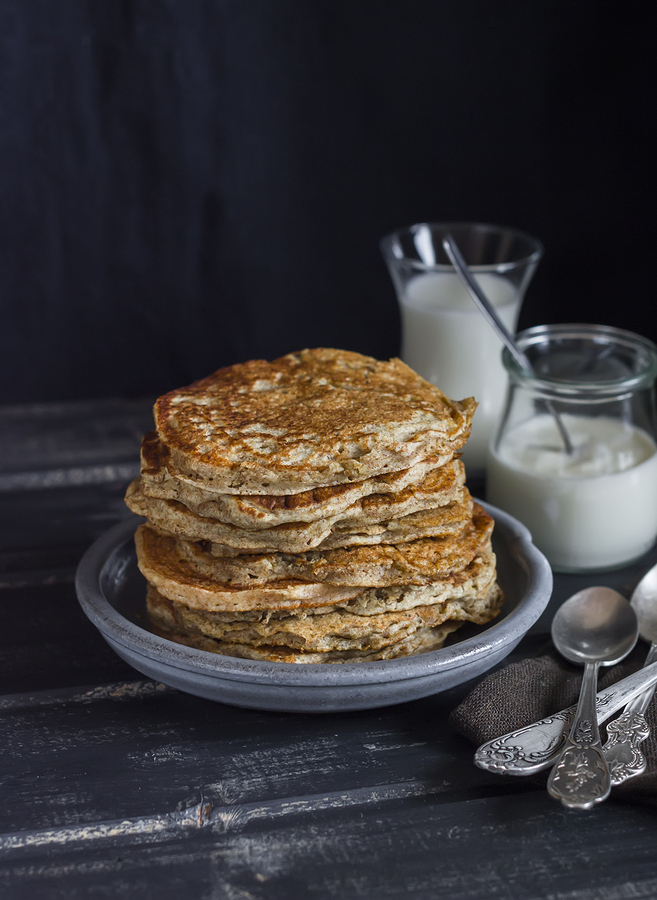 Healthy breakfast or snack - whole grain pancake milk and cream on a dark wooden table