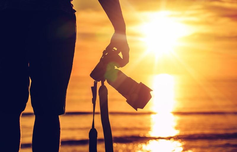 Sunset Photography. Photographer Ready to Take Sunset Pictures on the Beach. Professional Travel Photography Works.
