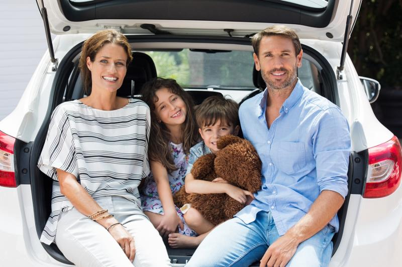 Family car trip on summer vacation. Happy smiling parents and two children in car having fun. Cute small boy holding teddy bear sitting with sister and parents in car for road trip with car.