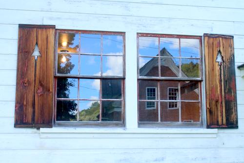Ski Warming Hut windows with Farmhouse reflection_ Gilbert_s Hill_ Woodstock. Photo by Rick Russell of the Vermont Standard.