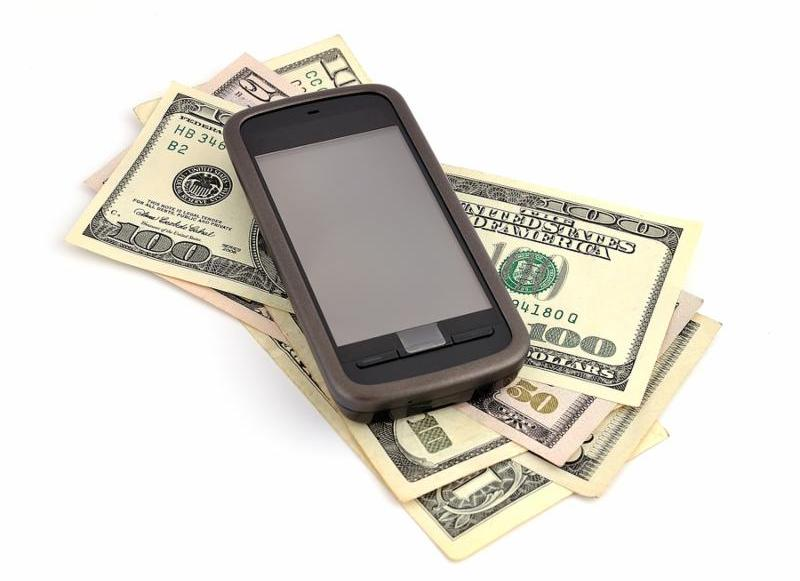 touchscreen mobile phone and dollars on white background