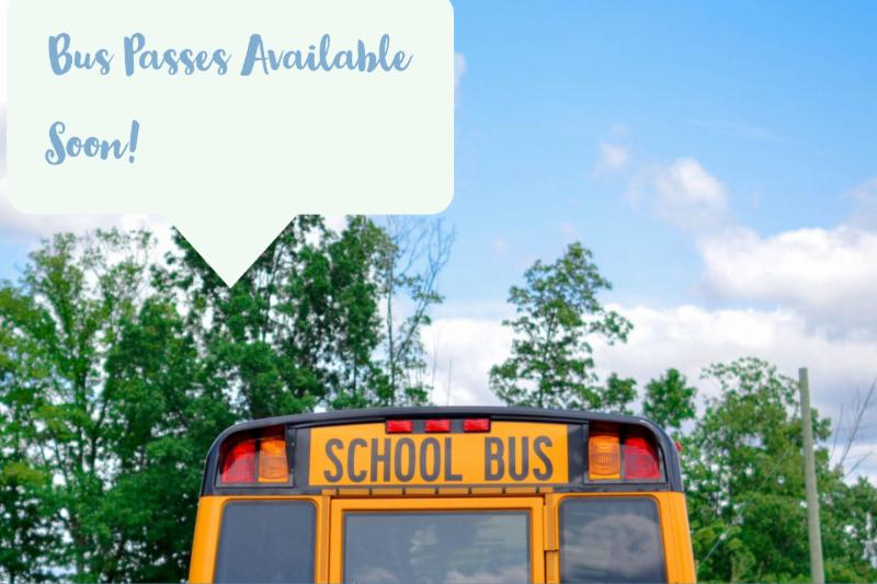 "School bus with trees and a blue, cloudy sky that says ""bus passes available soon!"""