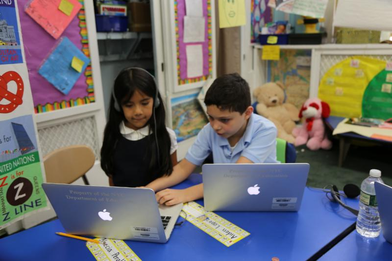 A girl and boy on apple laptops