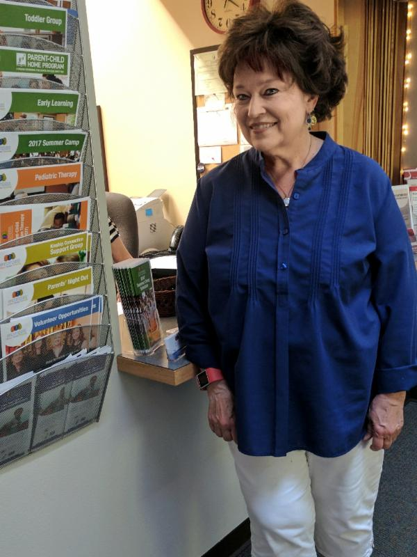 Kaye Moreton poses in front of the reception desk at the Early Learning Center