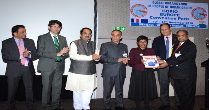 GOPIO Chairman Dr. Thomas Abraham presenting a book on GOPIO to Madame Ericka Bareights, French Minister for Overseas Affairs