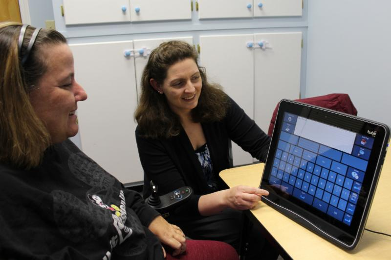 A speech language pathologist shows a client with ALS the features of a communication device