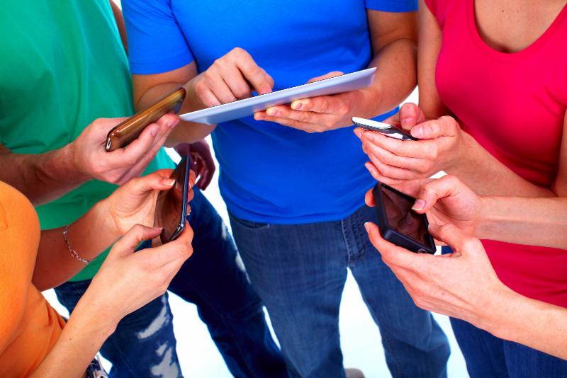 Four young people holding mobile devices