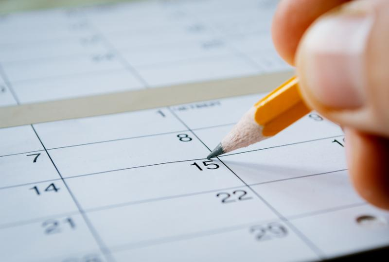 Person marking the date of the 15th with a pencil on a blank calendar with date squares as a reminder of an important day or to schedule a meeting or event     Note  Shallow depth of field