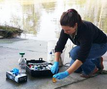 Texas Stream Team Volunteer sampling at water's edge
