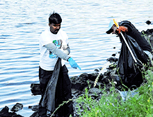 Two men picking up trash at the water's edge