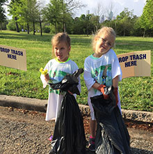 Two cute girls with trash bags at Trash Bash.