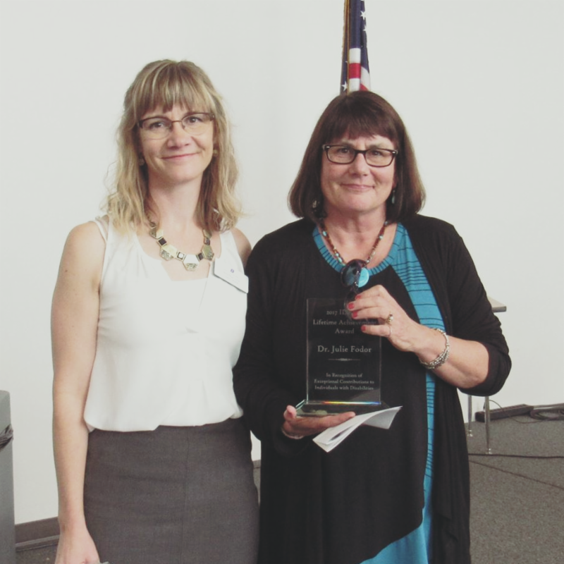 Julie Fodor (right) holding her Lifetime Achievement Award presented by Andrea Cox (left)