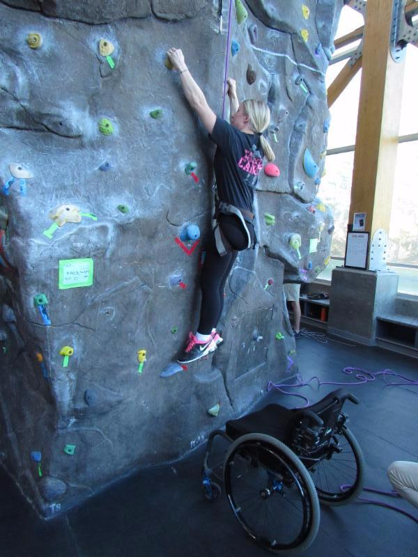 Climbing participant pulls herself up the climbing wall.